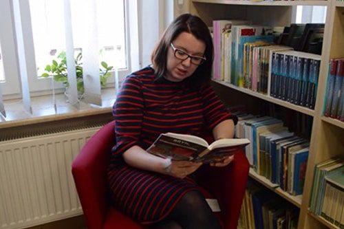kobieta czytająca ksiażkę na fotelu