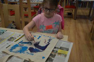 dziewczynka malująca sowę na torbę na książki