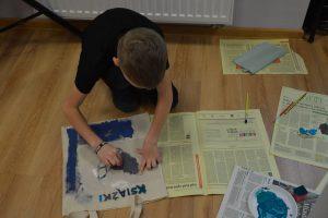 chłopiec malujący sowę na torbie na ksiażki
