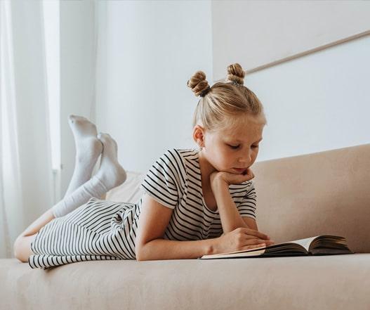 dziewczynka czytająca książkę leżąc na kanapie