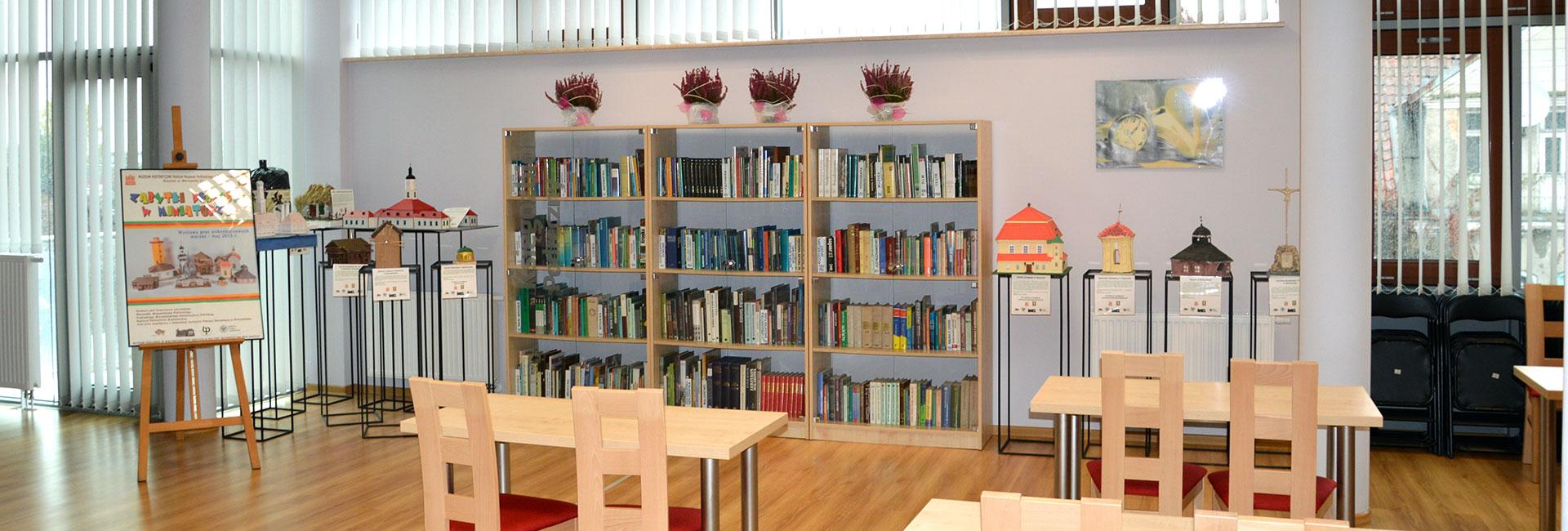 zdjęcie wnętrza sali bibliotecznej z regałami i stołami oraz krzesłami