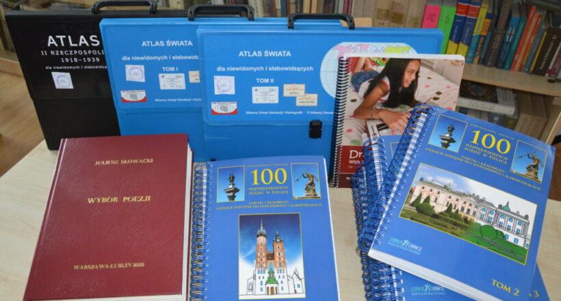 Książki i mapy w teczkach. W tle inne książki.