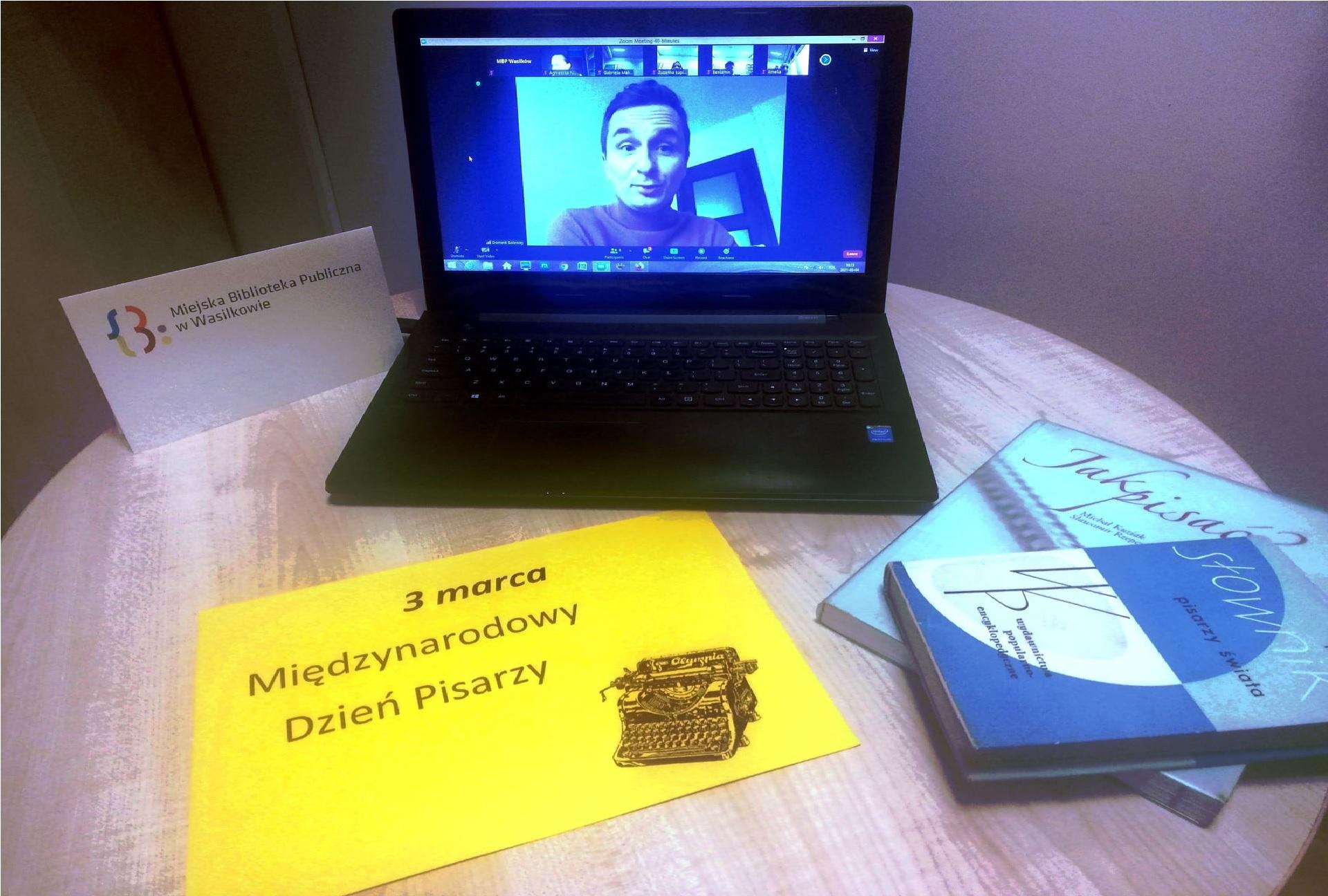 """Na stoliku laptop, książki, kartka z napisem """"3 marca Międzynarodowy Dzień Poezji"""" oraz logo Miejskiej Biblioteki Publicznej w Wasilkowie. Na ekranie laptopa mężczyzna."""