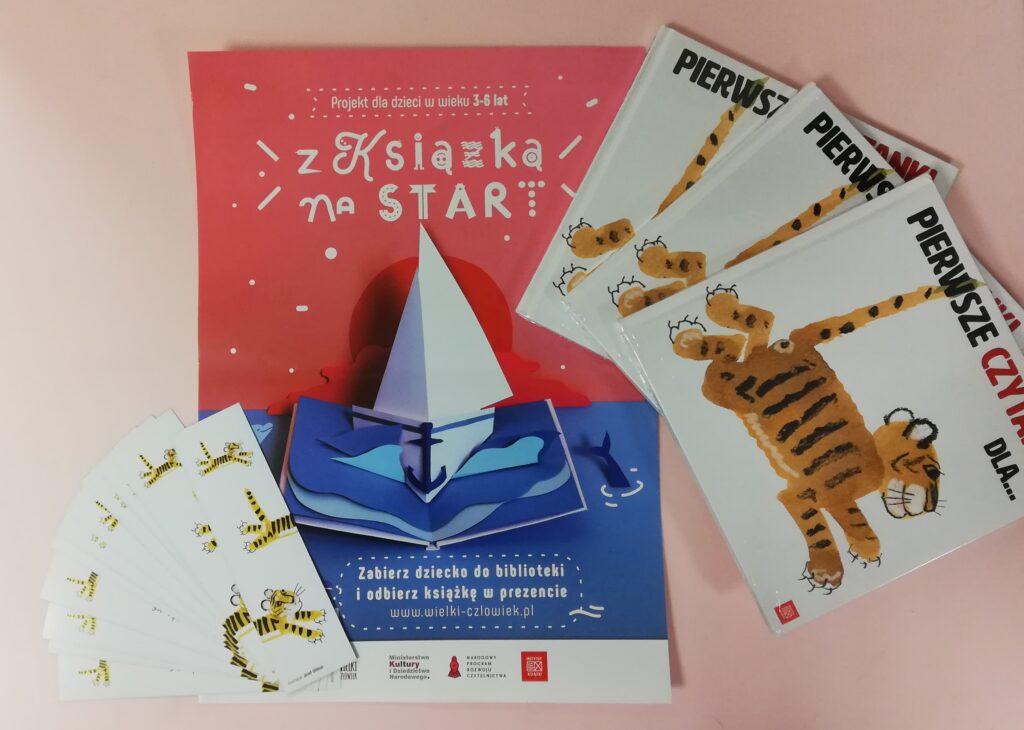 """Plakat projektu Mała książka wielki człowiek: Projekt dla dzieci w wieku 3-6 lat z książką na start. Zabierz dziecko do biblioteki i odbierz książkę w prezencie. Obok plakatu książki """"Pierwsze czytanki dla..."""" z tygrysem na okładce oraz zakładki do książek z tygrysami."""