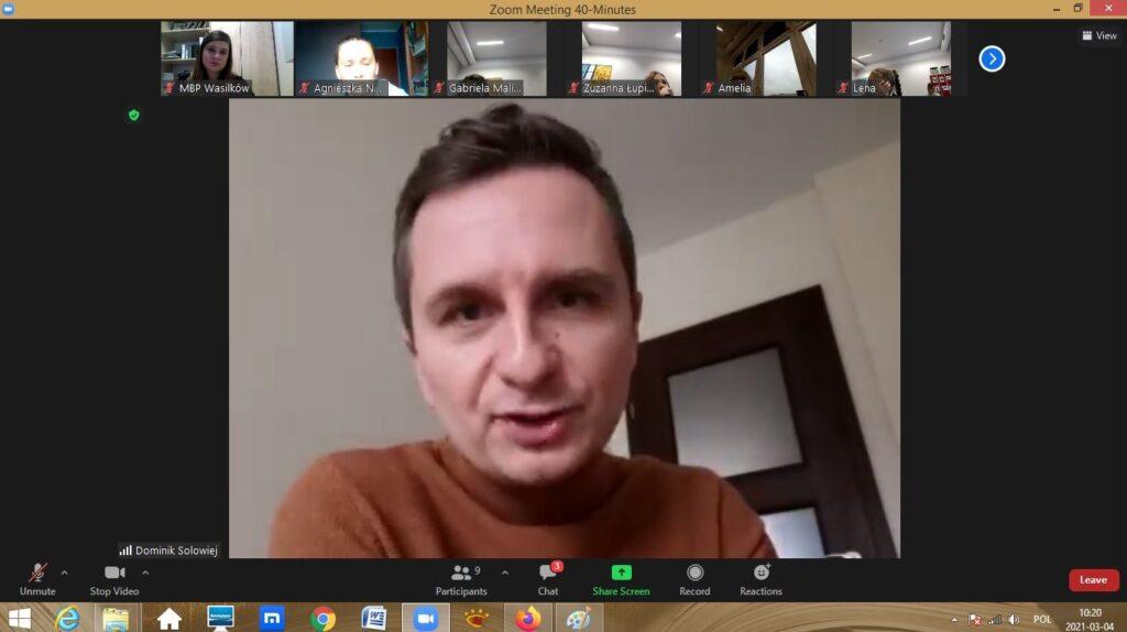 Zrzut ekranu z programu komputerowego - spotkanie online  - mężczyzna na pierwszym planie, na górze małe obrazki ze zdjęciami dwóch kobiet i 4 dzieci.