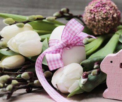Na zdjęciu kompozycja wielkanocna z kwiatów, bazi i pisanek, na pierwzym planie zając wielkanocny