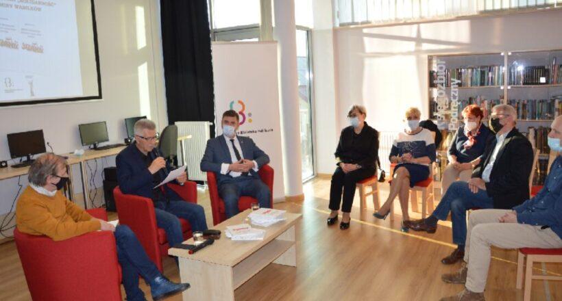 Troje mężczyzn siedzi przy stoliku, jeden przemawia przez mikrofon. Po drugiej stronie siedzi publiczność - trzy kobiety i dwóch mężczyzn.