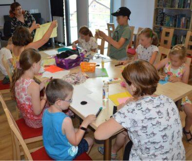 Dzieci wykonują prace plastyczne przy stoliku, na którym leżą różne przybory plastyczne. Nad dziećmi stoi kobieta.