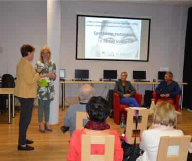 Dwie kobiety stoją przed publicznością siedzącą na krzesłach w bibliotecznej sali. Obok nich siedzą na fotelach kobieta i mężczyzna. Nad nimi znajduje się tablica z wyświetlonym slajdem promującym spotkanie autorskie z Tanyą Valko. W tle widać krzesła, stoły i komputery.