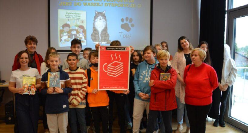 Uczestnicy spotkania autorskiego pozują do wspólnego zdjęcia na tle slajdu z kotkiem wyświetlonego z rzutnika na tablicy, z plakatem promującym Dyskusyjne Kluby Książki.